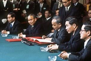 Ông Nguyễn Duy Trinh (giữa), đại diện Bắc Việt Nam, ký thỏa thuận ngừng bắn cuộc chiến Việt Nam, ảnh chụp ngày 27 tháng 1 năm 1973 tại Paris.
