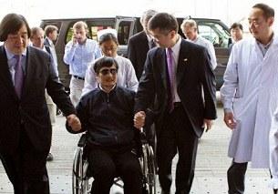 Nhà tranh đấu khiếm thị Trần Quang Thành (giữa) nắm tay đại sứ Mỹ Gary Locke (phải) trước lúc nhập viện.