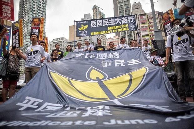 Người biểu tình ủng hộ dân chủ đứng đằng sau một biểu ngữ lớn tại Hồng Kông vào ngày 31 Tháng Năm năm 2015, trong một cuộc biểu tình tưởng nhớ đàn áp tại Quảng trường Thiên An Môn ở Bắc Kinh năm 1989