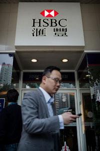 Một người Trung Quốc đi qua một chi nhánh ngân hàng HSBC tại Hồng Kông hôm 11/12/2012. HSBC đã đồng ý trả cho nhà chức trách Mỹ 1,92 tỷ USD để giải quyết những cáo buộc rửa tiền. AFP