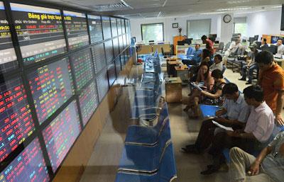 Các nhà đầu tư chứng khoán theo dõi giá cổ phiếu trên bảng điện tử tại một sàn chứng khoán ở Hà Nội hôm 25/8/2015. AFP