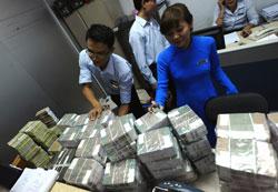 Nhân viên một chi nhánh ACB nhận tiền từ công ty mẹ để chi trả cho khách hàng rút tiền hàng loạt sau vụ bầu Kiên hôm 22/8/2012. AFP
