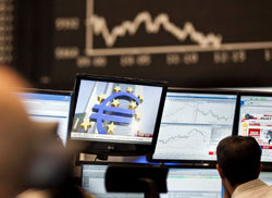 Các nhà đầu tư chứng khoán ngồi trước màn hình hiển thị các chỉ số DAX tại Sở Giao dịch chứng khoán Đức hôm 01/1/2012. AFP