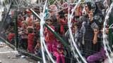 Hàng ngàn người tị nạn đứng đằng sau một hàng rào ở biên giới Hungary với Serbia gần thị trấn Horgos ngày 16 tháng Chín năm 2015.