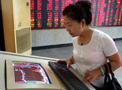 Một nhà đầu tư Trung Quốc nhìn vào giá cổ phiếu (màu đỏ cho giá tăng và màu xanh lá cây cho giá giảm) tại một nhà môi giới chứng khoán tại Thiên Tân, Trung Quốc hôm 09/8/2012. AFP photo