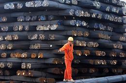 Một công nhân đang đứng trên các thanh thép ở một côn xưởng sản xuất thép tại Thanh Đảo, tỉnh Sơn Đông phía đông Trung Quốc tháng 4, 2014