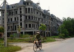 Một người dân đang đạp xe qua một dự án phát triển nhà xây dựng dở dang ở ngoại ô Hà Nội hôm 17/9/2012. AFP photo