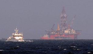 Một tàu cảnh sát biển Trung Quốc (trái) gần giàn khoan dầu của Trung Quốc trong vùng biển tranh chấp với VN ở Biển Đông hôm 14 tháng 5 năm 2014.