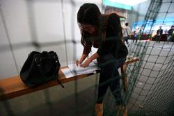 Một sinh viên đại học Trung Quốc chuẩn bị sơ yếu lý lịch tại hội chợ việc làm ở Thượng Hải, Trung Quốc, hôm 6 tháng 11 năm 2012. AFP PHOTO.