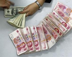 Một nhân viên ngân hàng đang xếp tiền đô la Mỹ và đồng nhân dân tệ của Trung Quốc tại một ngân hàng ở tỉnh Tứ Xuyên, Trung Quốc hôm 08/4/2010.