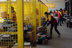 Nhân viên phân loại các gói hàng tại một công ty chuyển phát nhanh tại Beijing hôm 12/11/2013. AFP photo