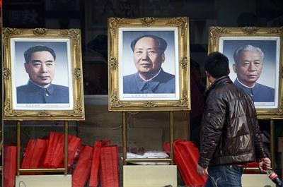 Một người đàn ông đang nhìn các bức chân dung của các cựu lãnh đạo Trung Quốc (từ trái sang) Chu Ân Lai, Mao Trạch Đông và Lưu Thiếu Kỳ khi ông đi ngang qua một studio ở Bắc Kinh, ảnh minh họa chụp trước đây. AFP PHOTO.