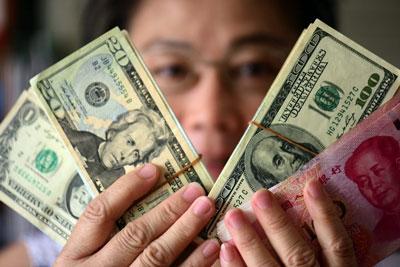 Một nhân viên ngân hàng ở Trung Quốc với đồng đô la và đồng nhân dân tệ tại một ngân hàng ở tỉnh Hải Nam hôm 10 tháng 10 năm 2016.