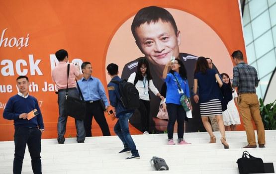 Các sinh viên Việt Nam tạo dáng bên cạnh một bảng quảng cáo có chân dung của tỷ phú người Trung Quốc và người sáng lập của Alibaba, Jack Ma.