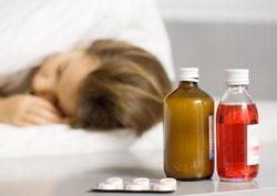 Ảnh minh họa một người bệnh với các loại thuốc ho để đầu giường. AFP photo