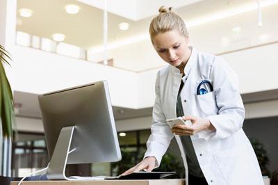 Một bác sĩ dùng iphone để làm việc cùng computer.