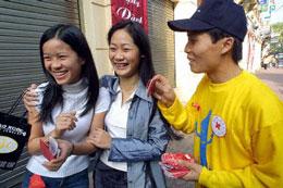 Tình nguyện viên chương trình phòng chống HIV/AIDS đang phân phát condom trên đường phố Hà Nội. AFP PHOTO