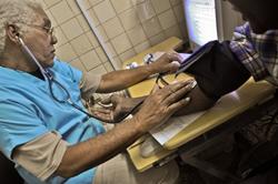 Bác sĩ đang đo huyết áp cho bệnh nhân ở Havana hôm 20/12/2010. AFP