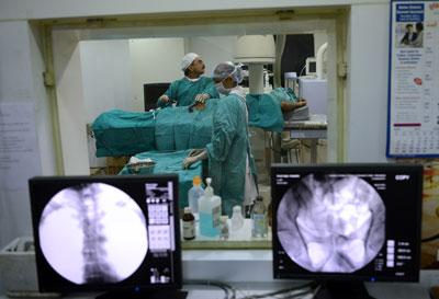 Bác sĩ phẫu thuật người Ấn Độ, Manish Raval (trái) truyền tế bào gốc cho bệnh nhân Sampath Kumar, người bị chứng suy thận mạn tính tại Bệnh viện thận ở Ahmedabad vào ngày 6 tháng 2 năm 2013.