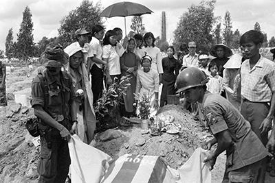 Một gia đình người Việt khóc thân nhân của họ, những người lính bị giết trên các mặt trận, tại Nghĩa trang Quân đội Quốc gia Biên Hòa, gần Sài Gòn. Ảnh chụp ngày 29 tháng 4 năm 1975. AFP PHOTO.