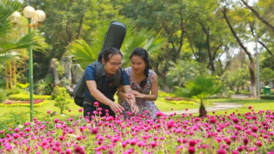 Ca nhạc sĩ khiếm thị Hà Chương đang nâng niu những đóa hoa ...