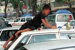 Một bé trai đang đánh bóng xe taxi tại Hà Nội. AFP PHOTO.