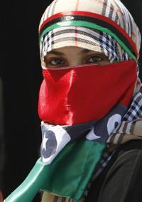 Một phụ nữ Libya quấn là cờ quốc gia Libya trước đây, nay được sử dụng bởi lực lượng nổi dậy. AFP photo