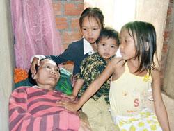 Bé Duyên và hai em bên giường bệnh của Mẹ, ảnh chụp tháng 6 năm 2011. Courtesy tnonline.