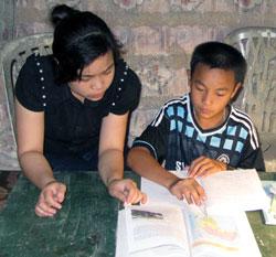 Bùi Thị Thảo đang chỉ bài cho em Bủi Đình Quang. Photo courtesy of dantri.com.vn