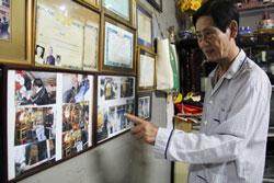 Ông Oanh bên những tấm ảnh người nghèo được ông chôn cất tử tế.