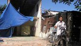 Anh Dương Văn Dũng trước căn nhà cũ dở dang, phải che bạt lại ở tạm để có chỗ đặt bàn thờ con trai.