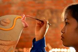 Một thiếu nữ Phù Lãng đang trang trí sản phẩm gốm. Photo courtesy of bacninh.gov.vn
