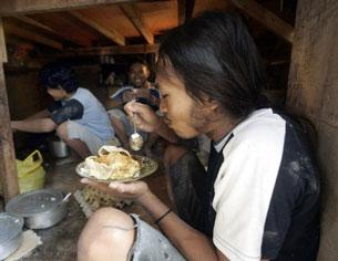 Công nhân ngoại quốc ăn trưa trong giờ nghỉ tại một xưởng làm ở Kuala Lumpur. AFP Photo