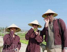 Du khách mặc chiếc áo nâu nông dân thưởng thức hương vị rau thơm Trà Quế. Courtesy Báo ảnh Vietnam