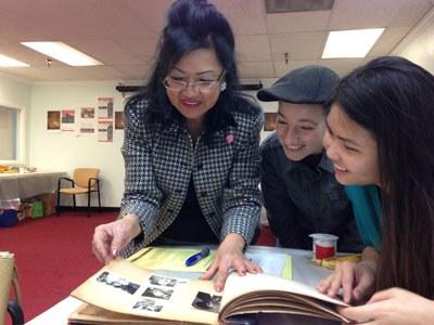 Bà Vân Lan (trái) đang chia sẻ hình ảnh gia đình mình với Cô Vũ Ngọc Trân (phải) điều phối viên Dự án Câu Chuyện Những Ngày Đầu Tiên. Photo courtesy of American Experience - PBS.
