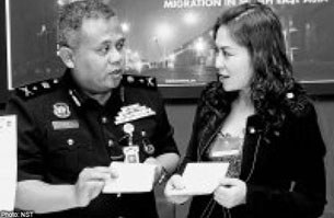 Cảnh sát Malaysia Datuk Abd Hassan  đang kiểm tra hộ chiếu của những cô gái Việt nam được giải cứu.