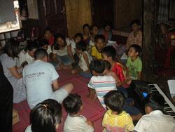 Các em nhỏ nguy cơ cao tại Kompong Luong, đang ngồi học giáo lý với Linh mục Nguyễn Bá Thông, ảnh chụp trước đây. Photo courtesy of OBV.