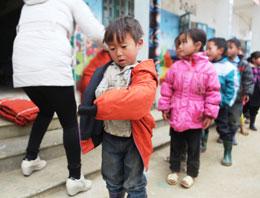Một em bé người sắc tộc H'mong đang mắc cái áo mới. RFA