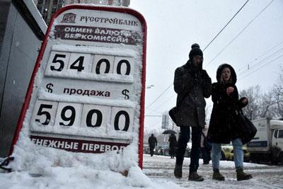 Bảng niêm yết giá ngoại tệ đối với đồng rúp của Nga bên ngoài một văn phòng giao dịch tại Moscow ngày 12 tháng 12 năm 2014. AFP photo
