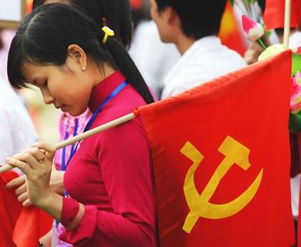 Một thiếu nữ cầm cờ cộng sản sau khi tham dự một cuộc diễu hành quân sự được tổ chức vào 10 tháng 10, 2010 tại Hà Nội