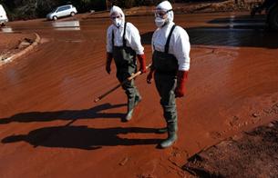 Nhân viên cứu hộ đi trên một con đường phủ đầy bùn đỏ ở Devecser, cách thủ đô Budapest 150 km về phía Tây, hôm 11/10/2010.  AFP Photo.