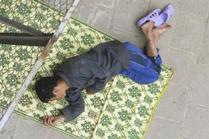 Một con nghiện ngủ trên đường phố Hà Nội. AFP PHOTO.