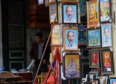 Hình cố chủ tịch Hồ Chí Minh được bày bán cùng các hình ảnh về tôn giáo tại một cửa hàng ở Hà Nội ngày 08 tháng 12 năm 2015. AFP photo