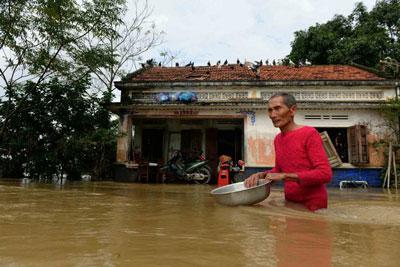 Một người đàn ông lội qua nước lũ ngay trước nhà ông ở Bình Định hôm 18/12/2016.