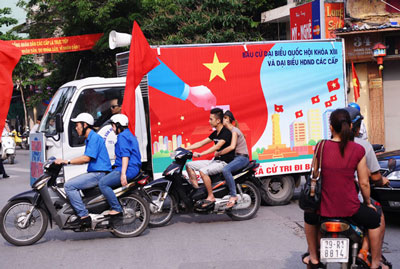 Những chiếc xe trang bị loa phóng thanh của một chế độ độc đảng đi kêu gọi bầu cử