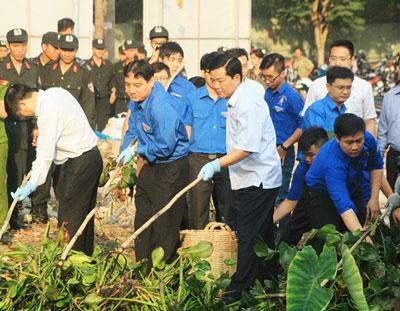 Ông Đinh La Thăng cùng dọn dẹp vệ sinh môi truờng với dân. Courtesy of baomoi.com