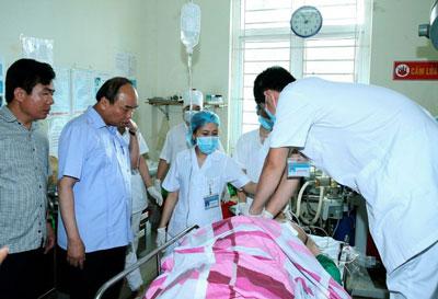 Thủ tướng Việt Nam Nguyễn Xuân Phúc (thứ hai từ trái) bên nạn nhân Phạm Duy Cường tại bệnh viện Yên Bái sáng 18/8/2016. AFP