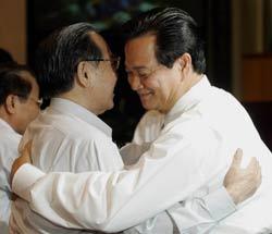 Thủ tướng Phan Văn Khải (T) chúc mừng tân Thủ tướng Nguyễn Tấn Dũng (P) trong buổi lễ nhậm chức của ông tại Quốc Hội hôm 27/6/2006. AFP photo