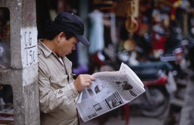 Một người dân phố cổ Hà Nội đọc báo.