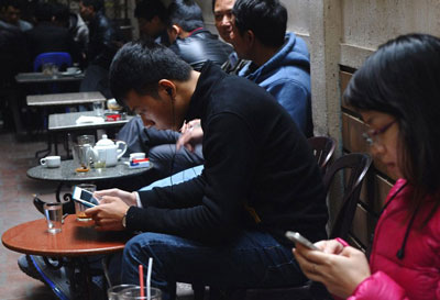 Giới trẻ VN sử dụng iPhone, iPad tại một quán cà phê vỉa hè Hà Nội năm 2013. AFP photo